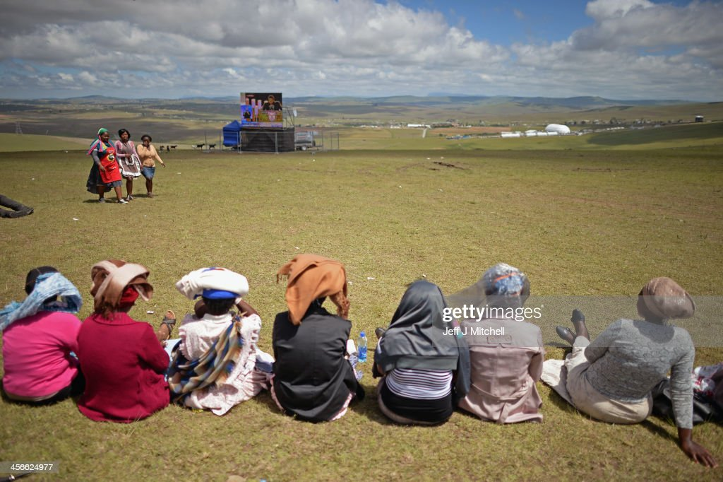 People watch the big screens at the site where former South African President Nelson Mandela will be buried on his family's property in his childhood village on December 15, 2013 in Qunu, South Africa. Mr. Mandela passed away on the evening of December 5, 2013 at his home in Houghton at the age of 95. Mandela became South Africa's first black president in 1994 after spending 27 years in jail for his activism against apartheid in a racially-divided South Africa.