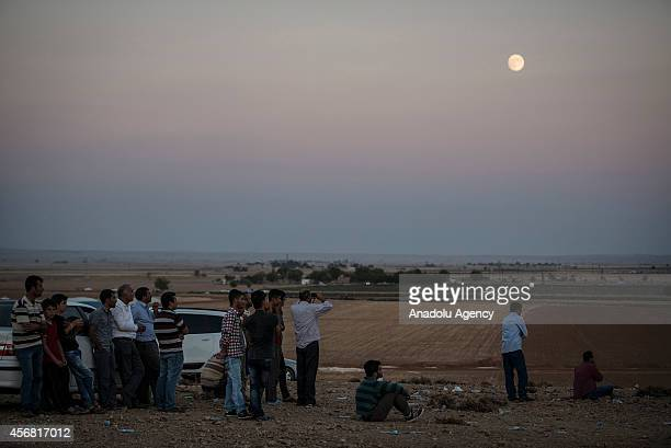 People watch the clashes between Islamic State of Iraq and the Levant and Kurdish armed groups in the Syrian border town of Kobani from Suruc...