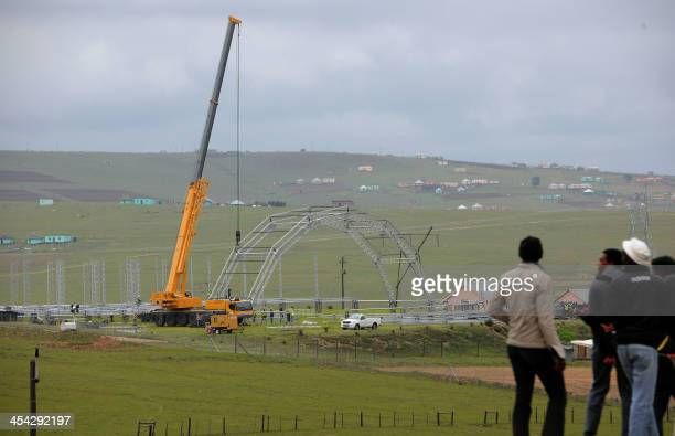 People watch the construction of a stage in Qunu on December 8 2013 ahead of the state funeral of former President Nelson Mandela who will be burried...