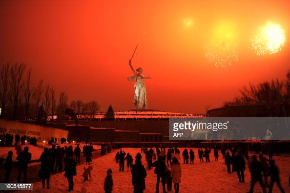 People watch the fireworks exploding over the giant Mother Motherland statue at the Stalingrad Battle memorial in the Russian city of Volgograd late...