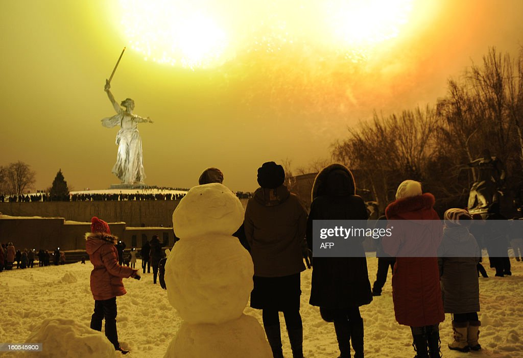 People watch the fireworks exploding over the giant Mother Motherland statue, at the Stalingrad Battle memorial, in the Russian city of Volgograd, late on February 2, 2013. Russia marked today the 70th anniversary of a brutal battle in which the Red Army defeated Nazi forces and changed the course of World War II.