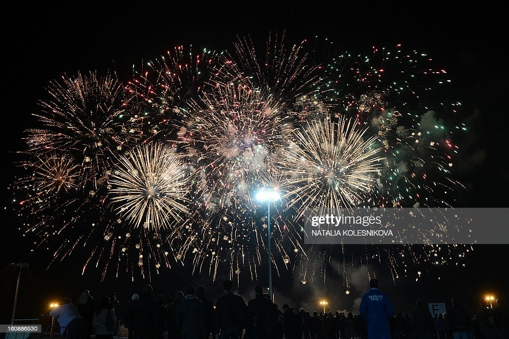 People watch the fireworks exploding over the Russian Black Sea resort of Sochi, on February 7, 2013, to celebrate the one year countdown to the Sochi 2014 Winter Olympics opening. Putin vowed today Russia would justify expectations when it hosts the Winter Olympic Games in Sochi in one year, after ruthlessly firing an official blamed for delays in building infrastructure. AFP PHOTO / NATALIA KOLESNIKOVA