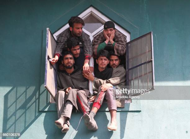 People watch the funeral ceremony of Hizbul Mujahideen rebel Tawseef Ahmad Wagay in south Kashmir's Kanjkul Yaripora some 60 kilometers from Srinagar...