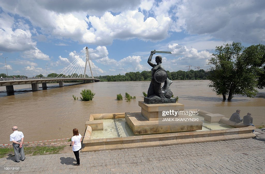 People watch the high water of the Wisla river next to a mermaid statue, or syrenka, the symbol of Warsaw, on May 21, 2010. Flash floods caused by days heavy rainfall have hit parts of central Europe, killing at least seven people, disrupting power supplies and forcing thousands of people from their homes. Southern Poland, parts of the Czech Republic and Slovakia and northern Hungary are among the worst affected regions