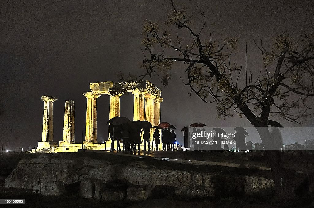 People watch the illuminated Temple of Apollon in Ancient Corinth during the inauguration of its lighting on January 26th, 2013, to attract both local and international tourists.