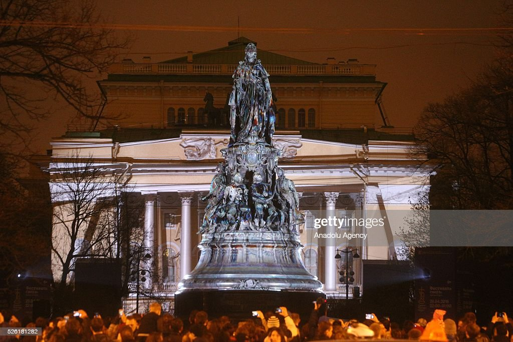 People watch the light projections on the building of the Alexandrinsky theatre and the memorial of Catherine the Great during the Light Festival in Saint-Petersburg, Russia on April 29, 2016.