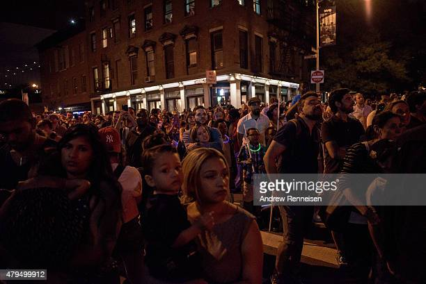 People watch the Macy's Fourth of July Fireworks from outside Brooklyn Bridge Park on July 4 2015 in the Brooklyn borough of New York City The...