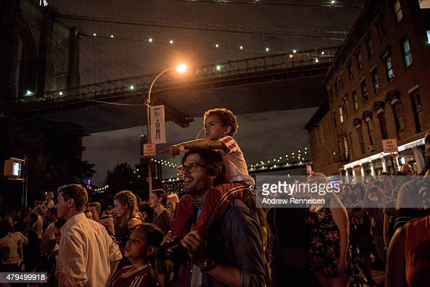 People watch the Macy's Fourth of July Fireworks from outside Brooklyn Bridge Park during on July 4 2015 in the Brooklyn borough of New York City The...