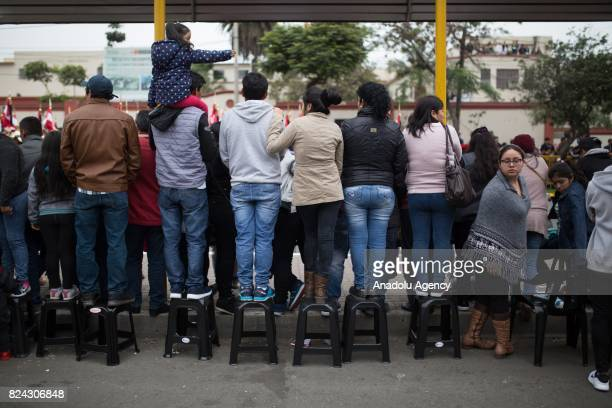 People watch the march of Peruvian troops on tabourets during a military parade within the celebrations for Peru's Independence Day in Lima Peru on...