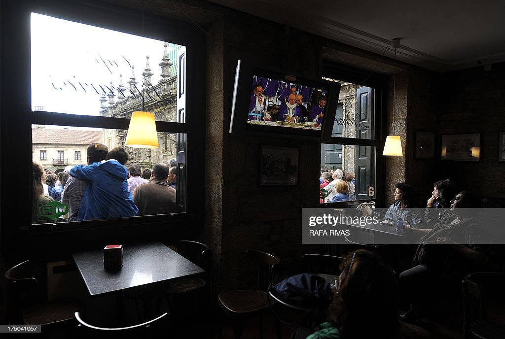 People watch the memorial ceremony of the victims of the derailed train of Angrois on a TV screen in a bar at the Quintana Square, behind the Cathedral of Santiago de Compostela on July 29, 2013. The driver of a train that hurtled off the rails in Spain was charged on July 28 with 79 counts of reckless homicide and released on bail after being questioned by a judge.