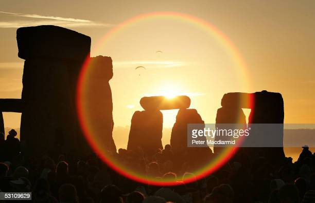 People watch the midsummer sun as it rises over the megalithic monument of Stonehenge on June 21 2005 on Salisbury Plain England Crowds gathered at...