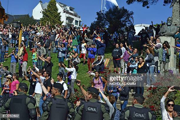 People watch the motorcade of US President Barack Obama as it drives by in Bariloche Argentina on March 24 2016 President Barack Obama paid homage...