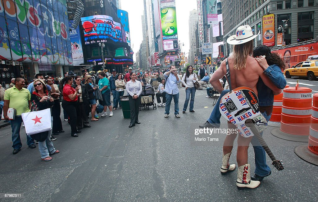People watch the Naked Cowboy perform on Broadway in Times Square after it was converted to a pedestrian zone May 26, 2009 in New York City. Sections of Broadway that pass through Times Square and Herald Square have been closed to vehicles in an effort by the city to reduce traffic and pollution while giving pedestrians more space.