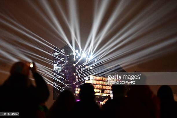 People watch the opening light show of the Elbphilharmonie concert hall in Hamburg northern Germany on January 11 2017 Around nine and a half years...