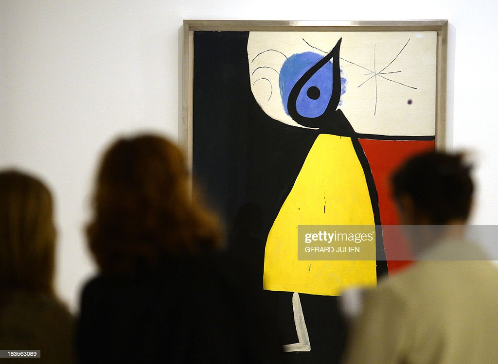 People watch the painting 'Mujer en la noche' by Joan Miro during the exhibition entitled 'Surrealism and the Dream' at the Thyssen-Bornemisza museum in Madrid, on October 7, 2013.