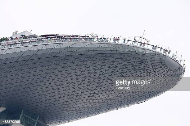 People watch the Republic of Singapore Air Force Black Knights perform a maneuver from the Marina Bay Sands SkyPark obersavation deck during an...