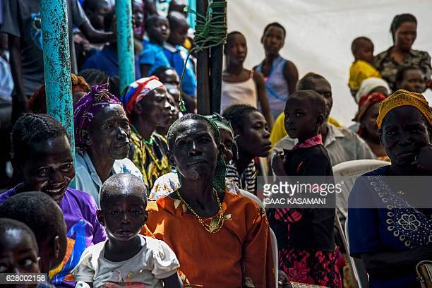 People watch the screening of the start of the ICC trial of former child soldierturnedwarlord Dominic Ongwen in Lukodi Uganda on December 6 2016...