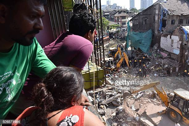 People watch the site of building collapse from a balcony at lane number 14 of Kamathipura on April 30 2016 in Mumbai India At least five people were...