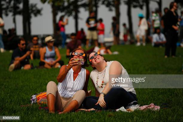 People watch the solar eclipse in front of the skyline of Manhattan as is seen from Hoboken New Jersey on August 212017
