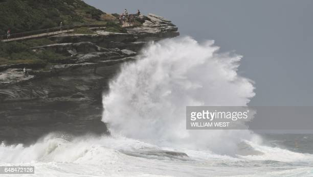 TOPSHOT People watch the spray as large seas pound the coast near Tamarama Beach in Sydney on March 6 2017 / AFP PHOTO / WILLIAM WEST
