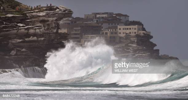 People watch the spray as large seas pound the coast near Tamarama Beach in Sydney on March 6 2017 / AFP PHOTO / WILLIAM WEST