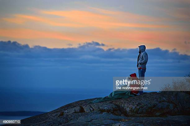 People watch the sunrise from Cadillac Mountain at Acadia National Park on Monday October 20 2014 in Bar Harbor ME The mountain reaches over 1500...