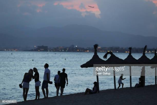 People watch the sunset at the beach on the Ballermann stretch on July 25 2017 in Palma de Mallorca Spain The term Ballermann which combines the...
