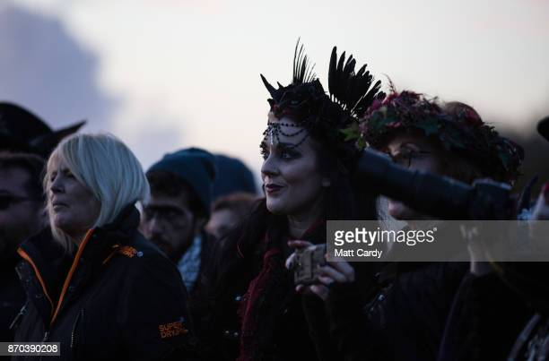 People watch the sunset ceremony on the lower slopes of Glastonbury Tor as they celebrate Samhain at the Glastonbury Dragons Samhain Wild Hunt 2017...