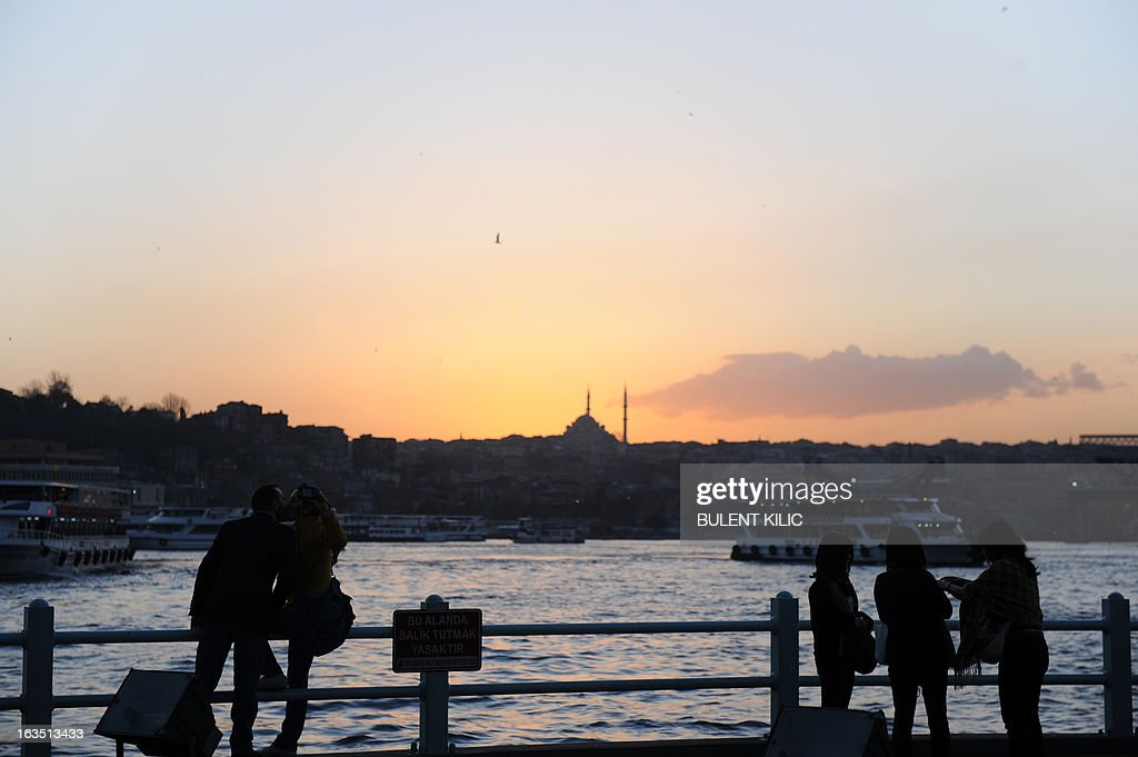 People watch the sunset in the Karakoy area of Istanbul on March 11, 2013.