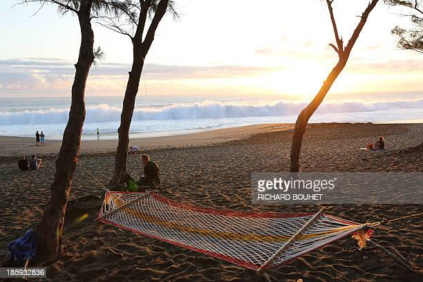 People watch the sunset near the beach area where a 24yearold man was attacked by a shark on October 26 in EtangSale a region of the La Reunion...