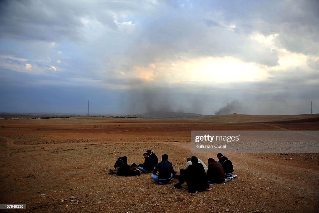 People watch the Syrian town of Kobani from a hill near the Mursitpinar border crossing on October 27, 2014 at the Turkish-Syrian border in the southeastern town of Suruc in Sanliurfa province. According to a Syrian activist group, the death toll has reached 815 during 40 days of fighting in and around the Syrian town of Kobani and the Britain-based Syrian Observatory for Human Rights reported the death toll for the Islamic State fighters stands at approximately 481 fighters. About 200,000 people have cross the border into Turkey for safety.