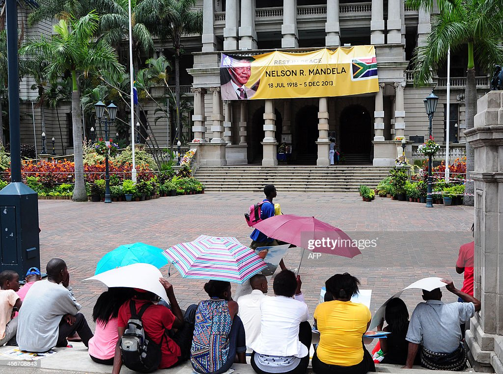 People watch the televised funeral of late South African former President Nelson Mandela on a giant screen set up for the event in the centre of Durban on December 15, 2013. Screens were set up in South Africa to allow people to watch Mandela's funeral taking place in his childhood village of Qunu on December 15, ending 10 days of national mourning and global tributes for the prisoner-turned-president who transformed his country and inspired the world.