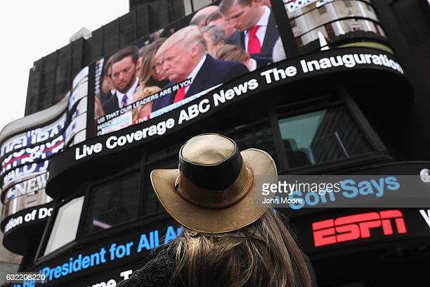 People watch the televised inauguration of Donald Trump as the 45th President of the United States while in Times Square on January 20 2017 in New...