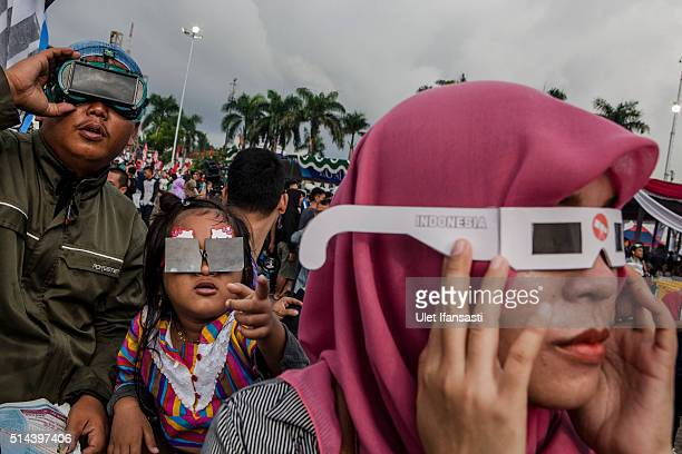 People watch the total solar eclipse in Palembang city on March 9 2016 in Palembang South Sumatra province Indonesia A total solar eclipse swept...