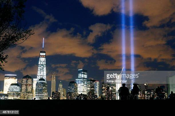 People watch the Tribute in Light as it shines over the New York Skyline on September 11 2015 in Jersey City New Jersey Today marks the fourteenth...