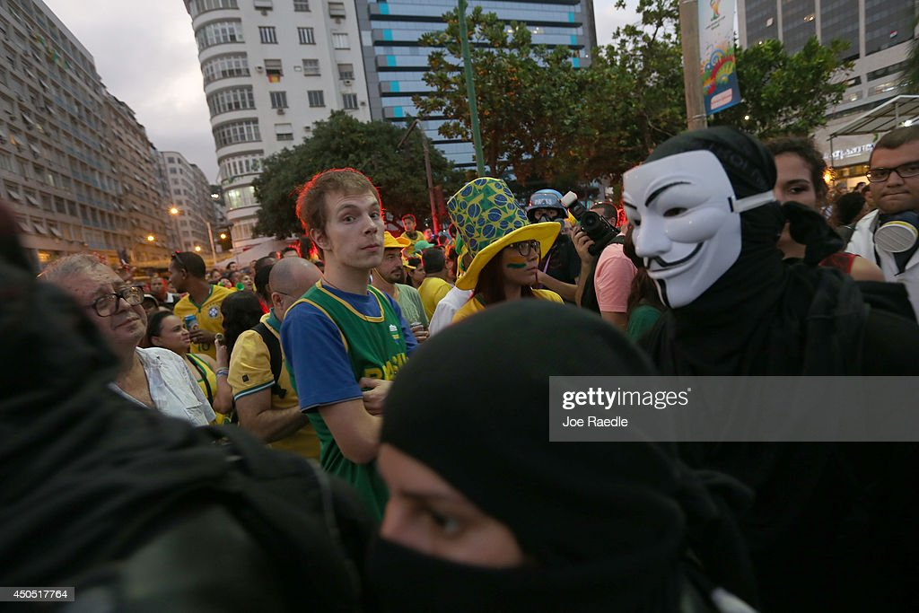 People watch the World Cup match on giant screens setup at the FIFA fan fest as anti-World Cup protesters pass by on Copacabana beach on June 12, 2014 in Rio de Janeiro, Brazil. Brazil defeated Croatia 3-1 in the first match of 2014 FIFA World Cup today.