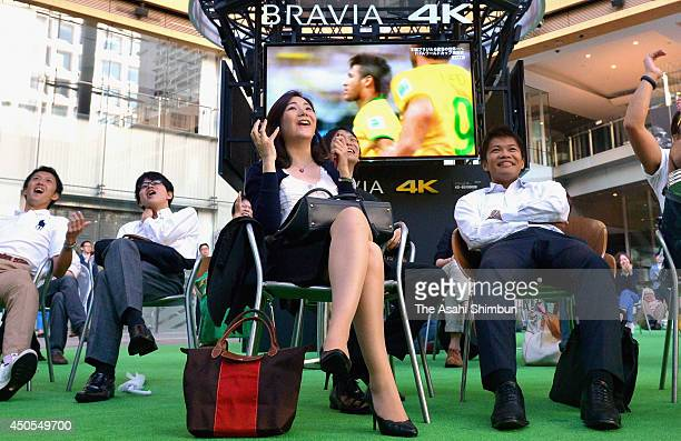 People watch the World Cup opening game between Brazil and Croatia during a public viewing site on June 13 2014 in Tokyo Japan