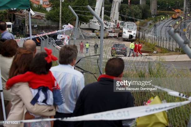 People watch the wreckage of the front locomotive standing on the road while workers repair the railway in Angrois on July 28 2013 in Santiago de...
