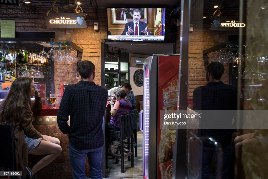 People watch through a bar window as King Felipe VI of Spain, addresses the nation regarding the Catalonian referendum vote, which took place last Sunday, on October 3, 2017 in Barcelona, Spain. According to the Catalonia's government more than two million people voted on Sunday in the referendum of Catalonia, which the Government in Madrid had declared illegal and undemocratic. Officials said that 90% of votes cast were for independence. The Catalan goverment's spokesman said that an estimated of 770,000 votes were lost as a result of 400 polling stations being raided by Spanish police. Hundreds of citizens were injured during the police crackdown.