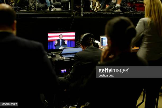 People watch US President Donald Trump addresses supporters on a monitor at the Indiana State Fairgrounds Event Center September 27 2017 in...