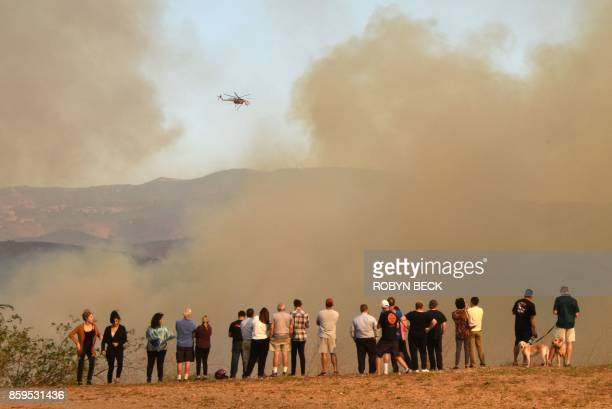 TOPSHOT People watch waterdropping helicopters amidst smoke from the Canyon Fire 2 October 9 2017 in Orange California / AFP PHOTO / Robyn Beck