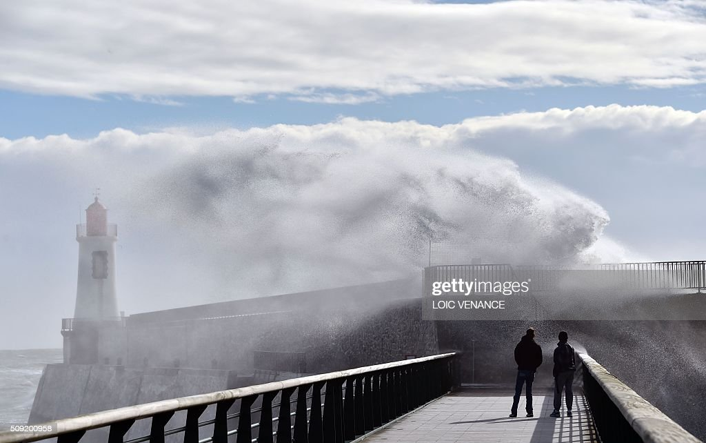 People watch waves breaking against a pier in Les Sables-d'Olonne, western France, on February 9, 2016. High winds buffeted northwestern Europe on February 8, leaving one woman in France in a coma after she was hit by an advertising hoarding. Electricity was cut to 5,000 homes in northern France. / AFP / LOIC VENANCE