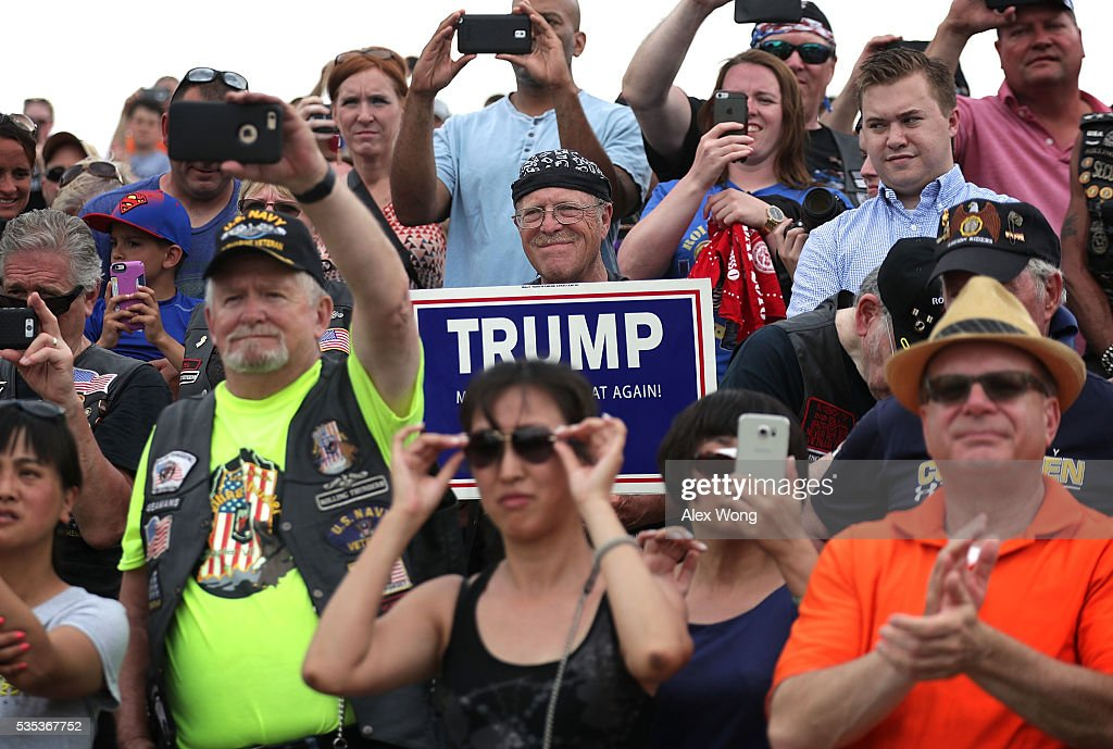 People watches as Republican presidential candidate Donald Trump speaks during the annual Rolling Thunder First Amendment Demonstration Run May 29, 2016 in Washington, DC. Bikers are gathering in the annual parade in the nation's capital to remember those who were prisoners of war and missing in action on Memorial Day weekend.