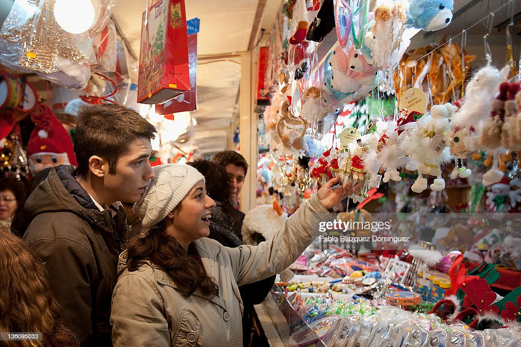 People watches Christmas items at a shop in a Christmas market fair at Plaza Mayor Square six days before Christmas Day on December 19, 2011 in Madrid, Spain. This year businesses are starting sales and discounts before Christmas to try and gain customers during the current economic crisis.