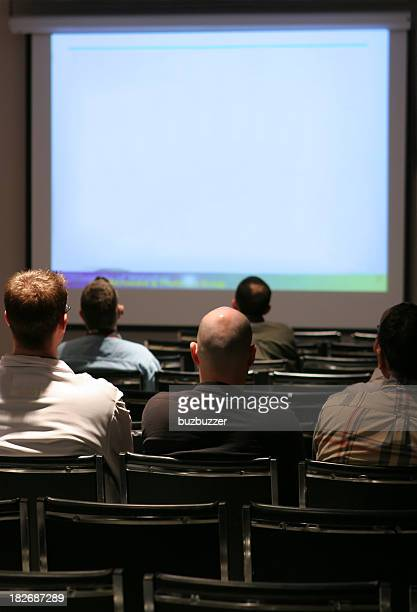 People watching a presentation on a large screen