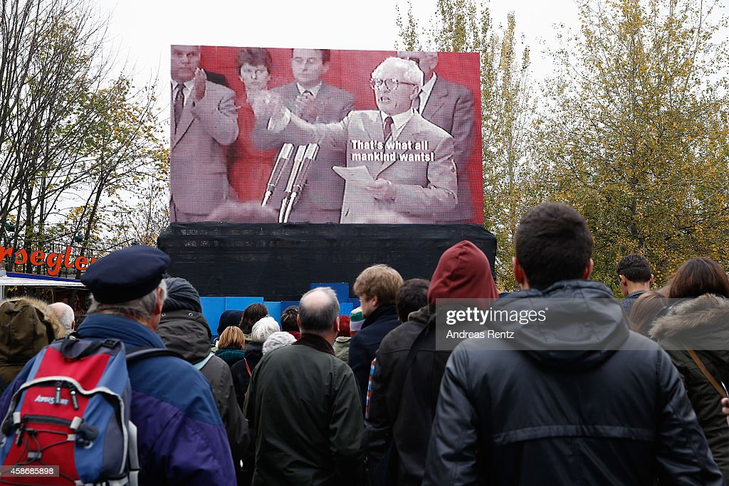 People watching a screening that pictures East German leader <a gi-track='captionPersonalityLinkClicked' href=/galleries/search?phrase=Erich+Honecker&family=editorial&specificpeople=209084 ng-click='$event.stopPropagation()'>Erich Honecker</a> during an information video about the fall of the Berlin wall on the 25th anniversary of the fall of the Wall on November 9, 2014 in Berlin, Germany. The city of Berlin is commemorating the 25th anniversary of the fall of the Berlin Wall with an installation of 6,800 lamps coupled with illuminated balloons along a 15km route where the Wall once ran and divided the city into capitalist West and communist East. The fall of the Wall on November 9, 1989, was among the most powerful symbols of the revolutions that swept through the communist countries of Eastern Europe and heralded the end of the Cold War. Built by the communist authorities of East Germany in 1961, the Wall prevented East Germans from fleeing west and was equipped with guard towers and deadly traps.