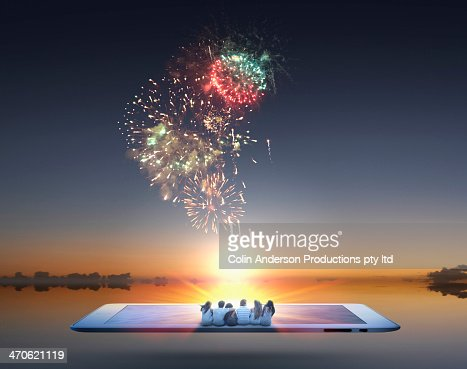 People watching fireworks erupt from digital tablet