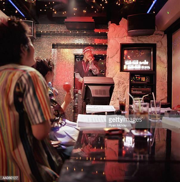 People watching man sing at karaoke bar (blurred motion)