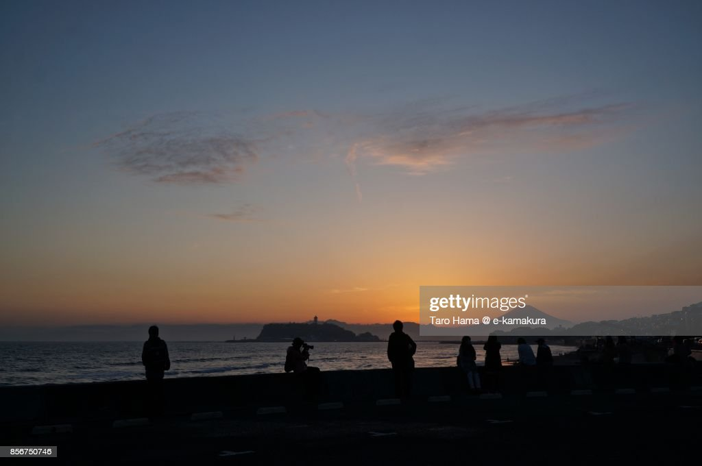 People watching Mt. Fuji and Enoshima Island on the sunset beach in Kamakura city in Kanagawa prefecture in Japan : ストックフォト