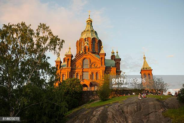 People watching sunset at Uspenski Cathedral in Helsinki, Finland